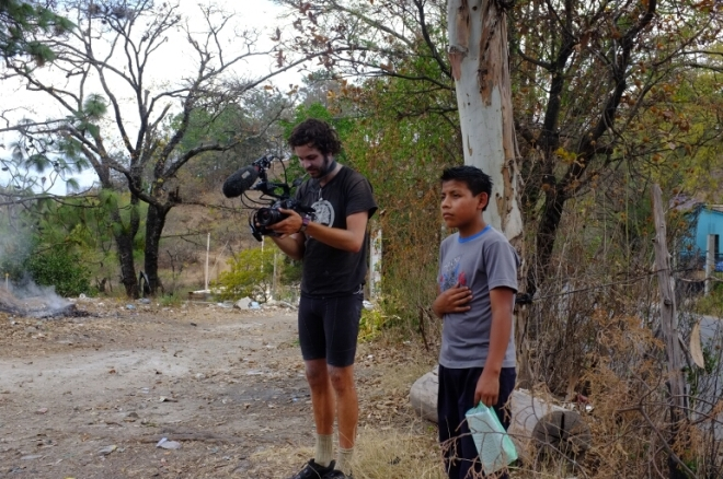 Guatemalan boy stands besideBike Tourer with video camera
